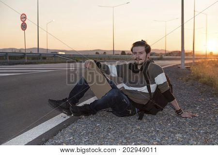 21 years old man sitting on the ground and hitchhiking
