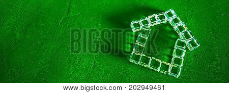 House made of ice cubes on a green background, the concept of real estate and ecology, border design panoramic banner