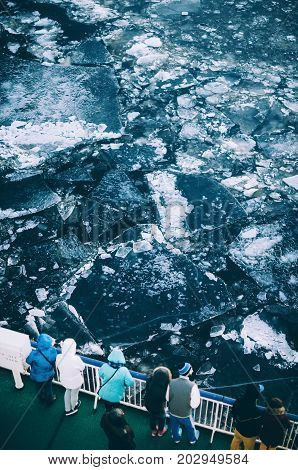 People dressed in warm clothes stand on deck of ship and watch cracked ice floes in sea in winter