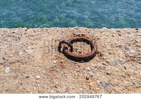 Old iron mooring cleat on a concrete pier
