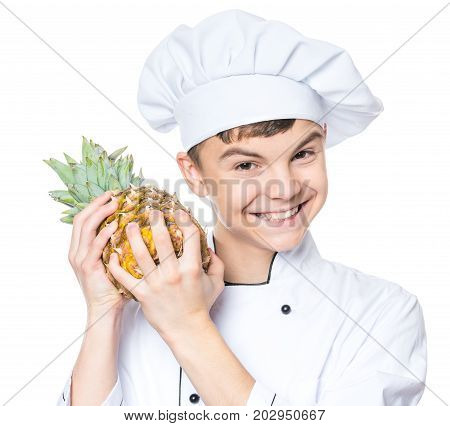 Handsome teen boy wearing chef uniform holding ananas. Portrait of a happy cute male child cook with pineapple, isolated on white background. Food and cooking concept.