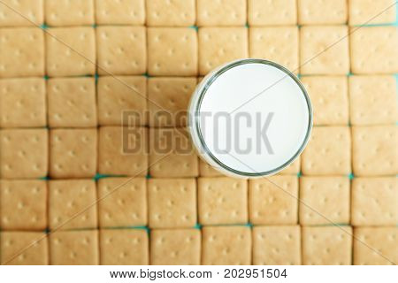 lots of crackers appetizing background. square crackers are laid out in rows on the crackers there is a glass with milk