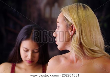 Young mad american blonde woman, looking angry to a foreign woman, racism, violence or discrimination concept in a blurred background.