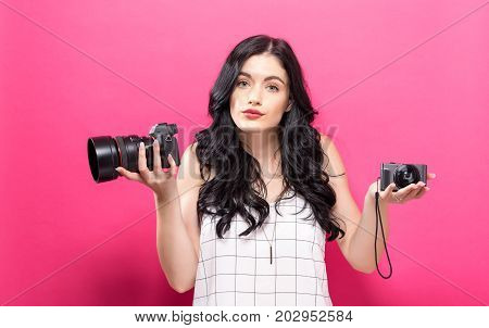 Young woman comparing professional and compact cameras on a solid background