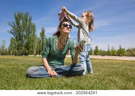little child playing to try to put a hat to mother with mobile phone sitting on green grass in public park named Juan Carlos in Madrid Spain Europe