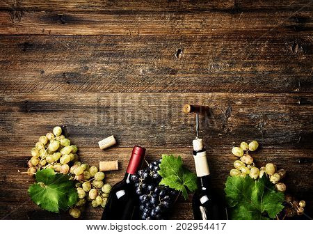 Wine bottles with grapes on wooden rustic background with copy space. Red and white wine. Top view.
