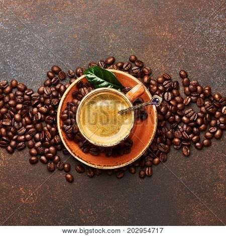 Coffee beans with cup of cofee on brown concrete table