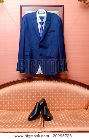 Dark Blue Suit, White Shirt And Necktie Hanging On The Wall Over Black Leather Shoes. Groom Clothing