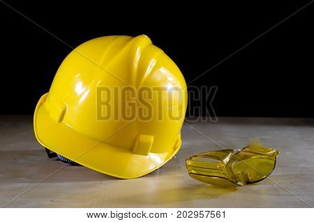 Yellow Helmet, Safety Goggles And Work Gloves For The Worker On A Light Wooden Table