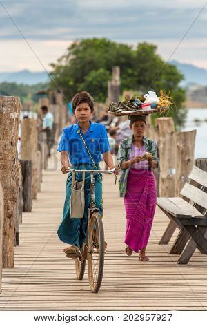 Amarapura, Myanmar - September 30, 2016: Burmese boy riding his bicycle on famous U-Bein bridge in Amarapura near Mandalay, Myanmar