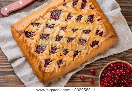 Pie with cranberries on a wooden table. Next to it lies a knife fresh and cranberries in a wooden plate. Decorated in a rustic style. Top view.