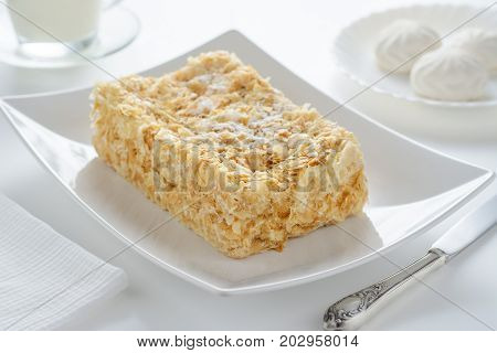 Cake Napoleon on a white plate on a light background
