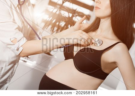 female medicine doctor holding stethoscope to pregnant woman standing for encouragement, empathy, cheering, support, medical examination. New life of abortion concept. Flare for text and design.