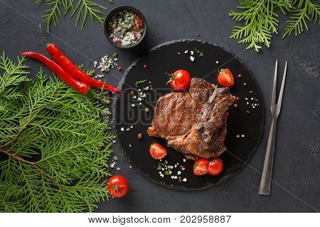 Rib eye steak on dark plate with thuja twigs board decorated with tomatoes, chilli, spices and meat fork, top view.