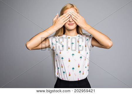 Portrait Of Young Scared Woman Covering Eyes With Hands While Standing Against Gray Studio Backgroun