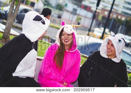 Close up of a happy group of friends having a fun conversation and wearing different costumes, one woman wearing a pink unicorn costume, other woman a panda costume and the man wearing a cat costume, in the city of Quito.