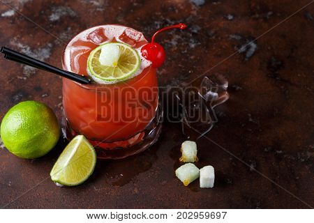 Red cocktail on brown background. Refreshing alcohol drink with tequila, citrus juice, lime and maraschino cherry on dark marbled table with melting ice and dices of refined sugar, copy space