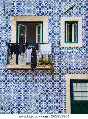 Traditional Portuguese tiles Azulejos on an old house with doors window and balcony. Hangin clothes on the balcony. Typical portuguese pattern. Frontal view.