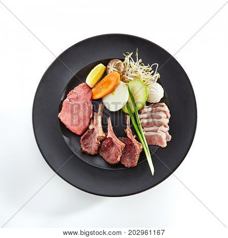 Preparation of raw foods for frying on teppan. Teppanyaki Japanese and Korean Grill Food - Marbled beef, rack of lamb, duck breast, all served with vegetables on white isolated background. Top viw