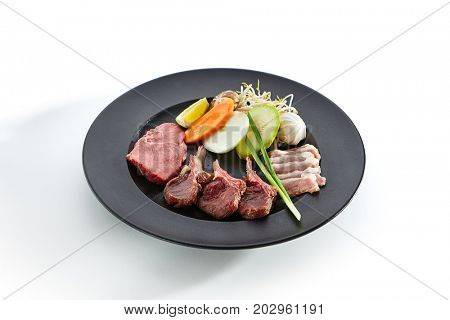 Preparation of raw foods for frying on teppan. Teppanyaki Japanese and Korean Grill Food - Marbled beef, rack of lamb, duck breast, all served with vegetables on white isolated background