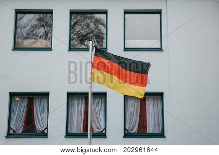 German flag on the outside of the building next to the windows. Patriotic sentiments before the elections. National flag.