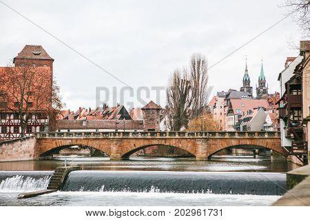 View of the pedestrian bridge and various buildings and houses in winter in Nuremberg in Germany.