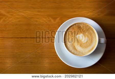 White cup of coffee on wooden table background top view. Cappuccino latte in cafeteria.