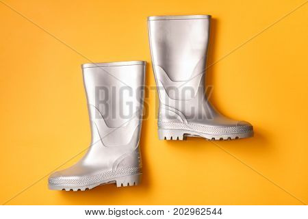 Autumn bright composition: Stylish silver gumboots. Yellow background Top view. Flat lay.