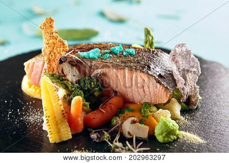 Fillet of river trout with crab mash, pumpkin and green peas with seasonings of herbs and fresh vegetables and mushrooms on black stone plate. Gastronomic restaurant menu