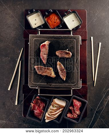 Meat platter on black stone and cups with three kinds of sauces sprinkled with herbs. Gastronomic restaurant menu. Top view