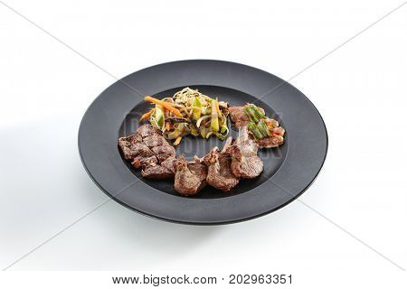 Teppanyaki Japanese and Korean Grill Food - Marbled beef, rack of lamb, duck breast, all served with vegetables sprinkled with sesame seeds and fresh herbs in black plate on white isolated background