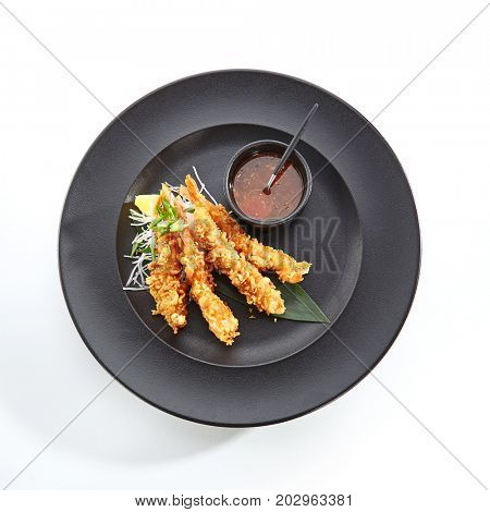 Teppanyaki Japanese and Korean Grill Food - tiger prawns in batter with daikon and spicy sauce with fresh herbs on black plate. Top View