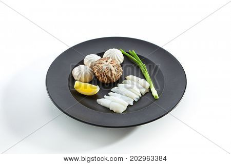 Teppanyaki Japanese and Korean Grill Food - Squid with mushrooms with an lemon slice and fresh herbs on black plate on white isolated background. Raw products for frying.