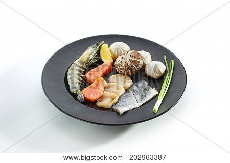 Teppanyaki Japanese and Korean Grill Food - Salmon, sea bass, shrimp 6/8, sea scallop garnished with vegetables, herbs and mushrooms on plate on white background. Raw ingredients for frying on teppan