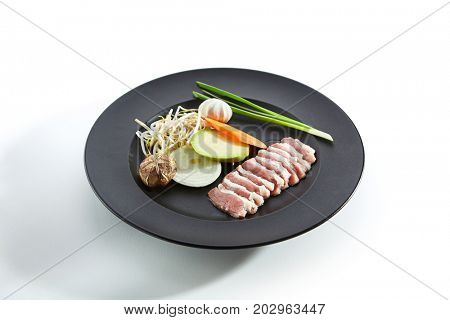 Teppanyaki Japanese and Korean Grill Food - Duck Breast with Vegetables with greens and mushrooms on black plate on white background. Preparation of raw ingredients for frying on teppan