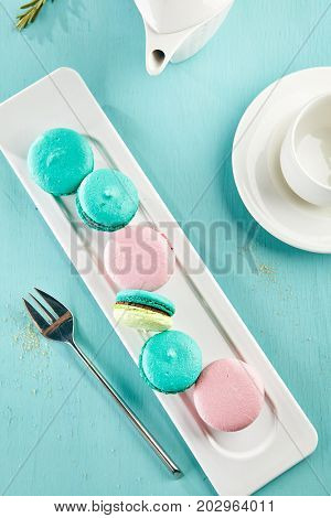 Dessert at the restaurant. Bright colored macaroons lie on white elongated ceramic plate against  background of blurry cups and saucers on azure wooden table