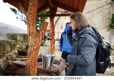 Tourist drinking water from the well of Motsameta Monastery located on breathtaking cliff-top promontory above a bend of the Tskhaltsitela River. Kutaisi Georgia.
