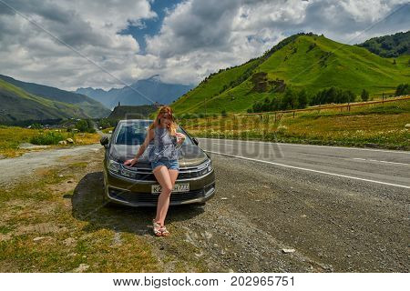 GEORGIAN MILITARY ROAD, GEORGIA - 29 JULY 2017: Young woman in front of Citroen car against Georgian Military Road Background