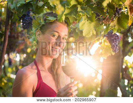 Wine queen visiting her vineyard with sun shining though the vines
