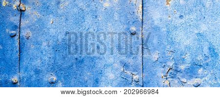 old rusty iron plate with blue varnish and many rusty bits and sheets