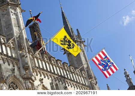 The old town hall of Bruges with blue sky and the waving flags of Belgium, Flanders and Bruges.