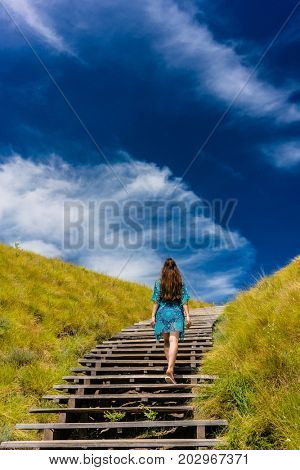 Full length rear view of a young woman wearing a blue dress while climbing wooden stairs outdoors in an idyllic travel destination from Indonesia