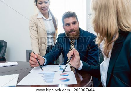 Business analyst smiling while interpreting financial reports showing profit and development during meeting with his female colleagues in the office