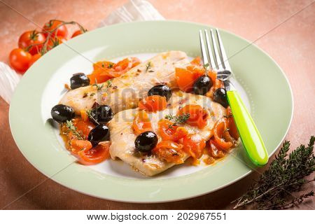 escalope with tomatoes olives and thymus, selective focus