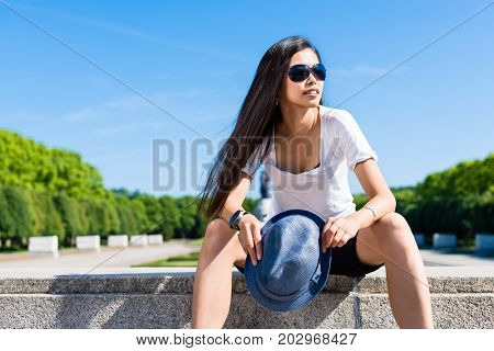Fashionable young Asian woman smiling while sitting down in the park