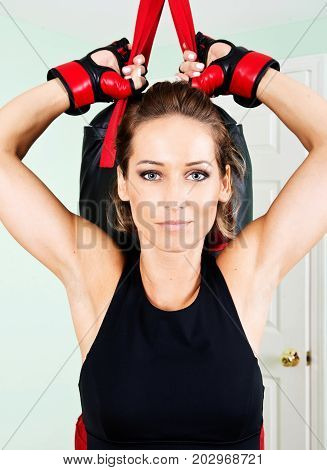 Young active woman workout: cardio kickboxing, punching bag in homemade gym, fitness