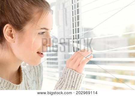 Beautiful young girl separating slats of blinds and looking through window
