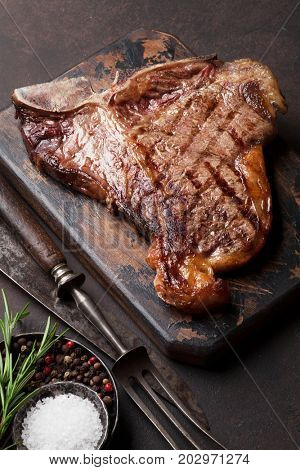 Grilled T-bone steak on stone table. Top view