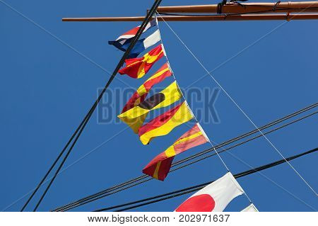 Sailboat with various flags from several countries hanging in a line from the masts on a sunny day with blue sky and space for text.