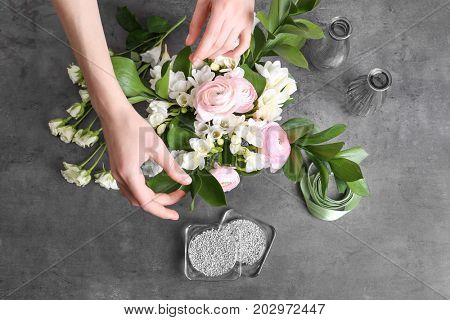 Female florist making beautiful bouquet with freesia flowers on gray background
